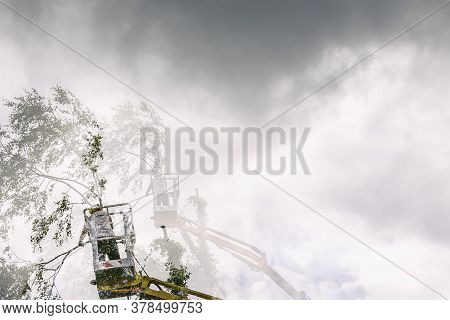 Double Exposure Of Arborist Man In The Air, Cloudy Sky, On Yellow Elevator, Basket With Controls, Cu