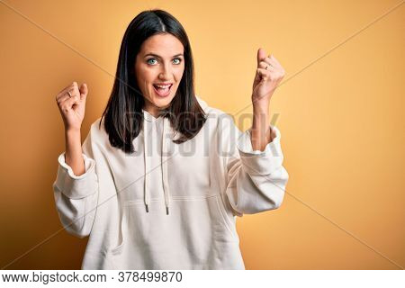 Young brunette sportswoman with blue eyes wearing training sweatshirt over yellow background celebrating surprised and amazed for success with arms raised and open eyes. Winner concept.