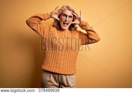 Middle age beautiful blonde woman wearing casual sweater and glasses over yellow background Smiling cheerful playing peek a boo with hands showing face. Surprised and exited
