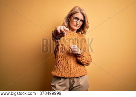 Middle age beautiful blonde woman wearing casual sweater and glasses over yellow background Punching fist to fight, aggressive and angry attack, threat and violence