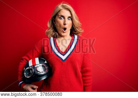 Middle age beautiful blonde motorcyclist woman holding moto helmet over red background scared in shock with a surprise face, afraid and excited with fear expression
