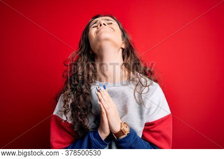 Young beautiful woman with curly hair wearing casual sweatshirt over isolated red background begging and praying with hands together with hope expression on face very emotional and worried. Begging.