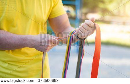 Man holding elastic rubber bands in hands outdoor