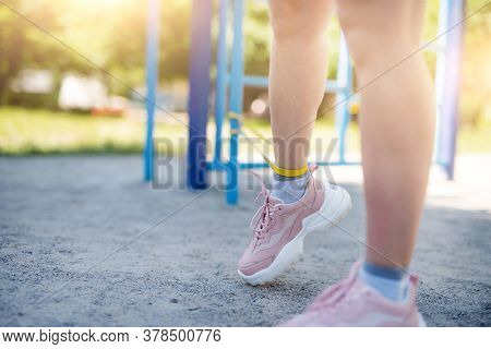 Woman training legs with elastic band in street, close up