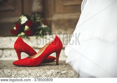 Red Shoes And Bouquet Next To Wedding Dress Of Bride