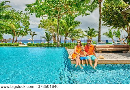 Family by poolside, young couple with three year old toddler boy. Resort swimming pool at Mahe, Seychelles.