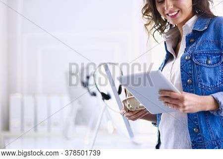 Smiling Woman Drinking Coffee And Using Tablet In The Cafe