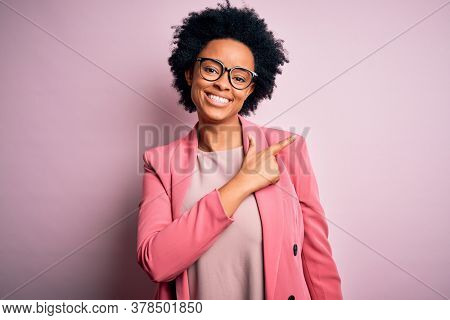 Young beautiful African American afro businesswoman with curly hair wearing pink jacket cheerful with a smile on face pointing with hand and finger up to the side with happy and natural expression