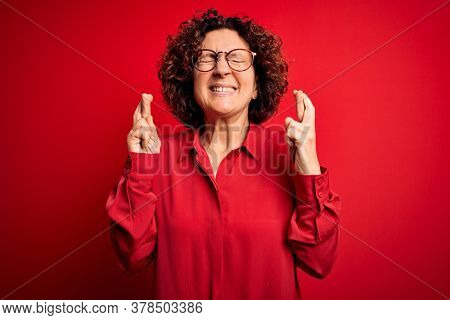 Middle age beautiful curly hair woman wearing casual shirt and glasses over red background gesturing finger crossed smiling with hope and eyes closed. Luck and superstitious concept.