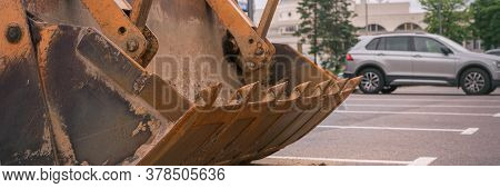 Yellow Metal Ladle Of Outdated Tractor On Grey Asphalt Parking Lot Against Silver Vehicle On Summer