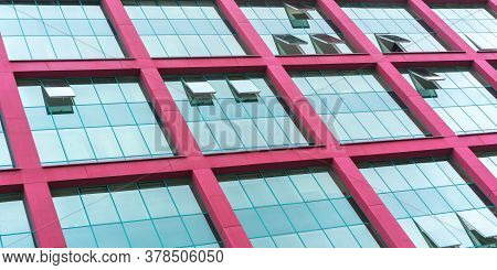 Commercial Office Building Wall With Skyscape Reflections In Large Panoramic Windows And Beams Of Re