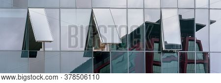 Commercial City Building Wall Of Panoramic Glass Windows Reflects Local Construction And Skyscape In