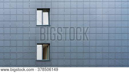 Small Windows With White Skyscape Reflections In Local City Building Wall With Grey Tiles Decoration