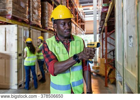 Portrait of african black warehouse worker hold hand scanner to do inventory work stock in distribution warehouse. Traceability FIFO LIFO inventory just in time and warehouse concept photo.