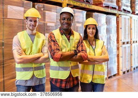 Portrait african black warehouse supervisor stand and crossed his arms with his interracial team in large warehouse distribution center. Business warehouse inventory logistic and teamwork concept