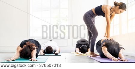 Panorama Asian sporty people learning Yoga class in fitness club. Instructor coaching and adjust correct pose on child pose to student. Yoga Practice Work out fitness healthy lifestyle concept.