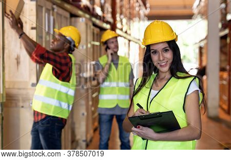 Portrait female white caucasian warehouse worker stand with clipboard and pen for inventory check with colleagues in large warehouse distribution background. Reopen business warehouse logistic concept