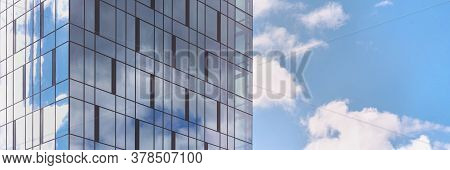 Large Local Skyscraper Of Blue Colour With Panoramic Windows Reflecting Skyscape With White Clouds O
