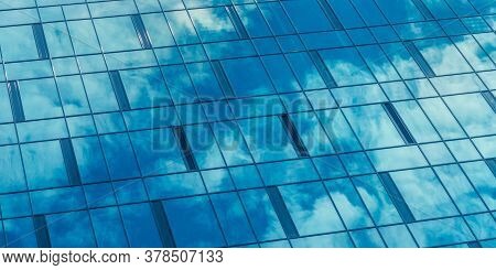 Blue Sky And White Clouds Reflect In Contemporary Highrise Building Panoramic Windows On Sunny Summe