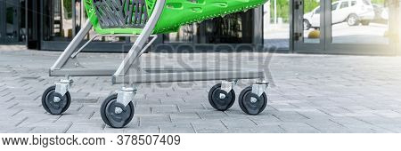 Grey Metal Supermarket Trolly Stands On Pavement Against Large Doors Reflecting Street On Sunny Summ