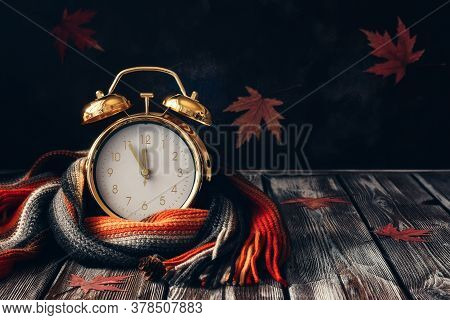 Conceptual Autumn Composition. Gold Alarm Clock Wrap Knitted Scarf On A Wooden Vintage Table And Dec
