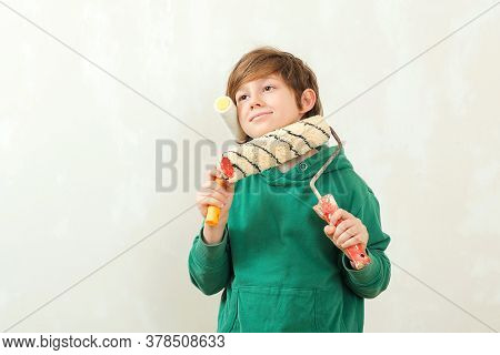 Son Helps Parents To Paint Wall. Boy Paints The Wall With A Roller. Cute Boy With Painting Roller. H