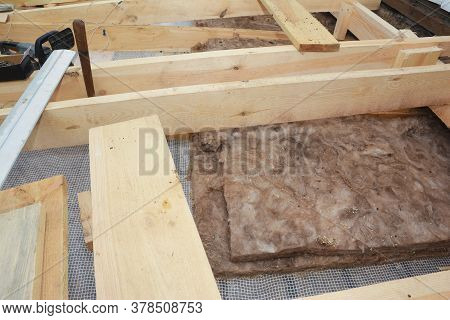 A Close-up On Roof, Attic Thermal Fiberglass, Mineral Glass Wool Insulation Under Wooden Roof Rafter
