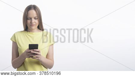 Young Caucasian Woman Texting On Her Mobile Phone And Looking At Phone Screen - Isolated Over A Whit