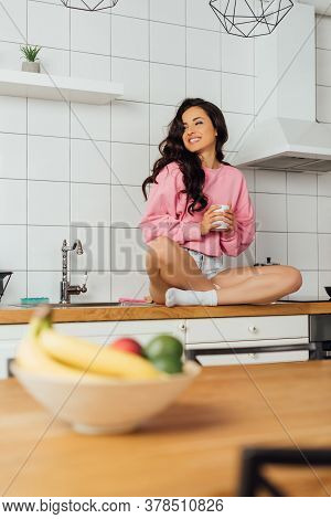 Selective Focus Of Attractive Positive Woman Holding Coffee Cup And Sitting On Worktop In Kitchen