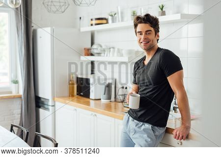 Selective Focus Of Handsome Man Smiling At Camera While Holding Cup Of Coffee Near Worktop In Kitche