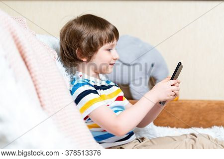 Happy Little Child Boy Playing Online Game, Watching Video On Cellphone, Sitting On Couch Entertaini