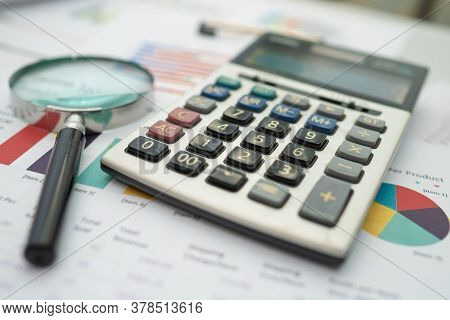 Magnifying Glass  And Calculator On Charts Graphs Paper. Financial Development, Banking Account, Sta