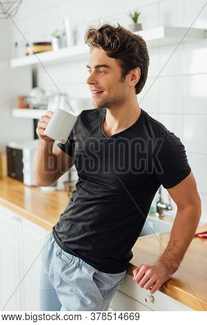Young Man Holding Cup Of Coffee And Smiling Away Near Worktop In Kitchen