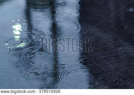 Rain Drops Rippling In A Puddle. The Street Light Refected In The Puddle Of Water