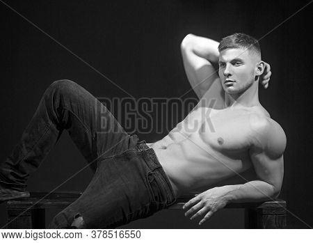 Brutal Sexuality, Sexy Man Lying In The Desk. Muscular Six Pack Man Shows Sexy Body.