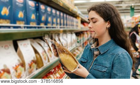 Shopping At The Grocery Store. A Young Beautiful Woman Holding A Package Of Pasta. In The Background