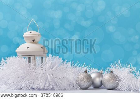 Christmas And Happy New Year Concept. White Lantern Silver Glitter Balls And Fluffy Tinsel. Copy Spa