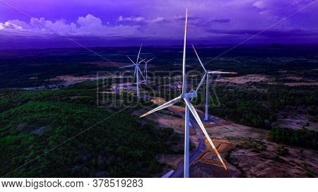 Wind Turbines Or Wind Power Generators At Sunset In The Evening. Alternative Green Ecological Power