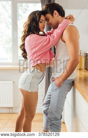 Side View Of Beautiful Woman Embracing Handsome Boyfriend Near Worktop In Kitchen