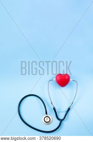 Stethoscope And Red Heart Overhead On Light Blue Backgroung With Space For Text