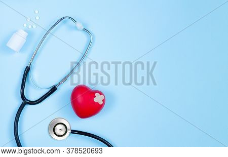 Medicine Stethoscope, Bottle Of Pills And Red Heart With Plaster Top View On Cardiologist Table