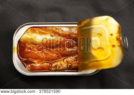 Canned Sardines In Tomato Sauce On A Black Background.