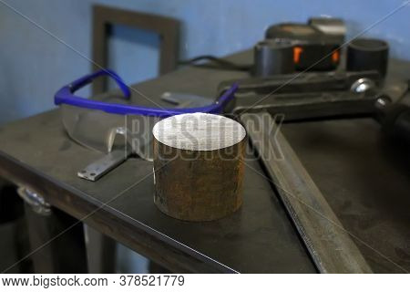 A Round Iron Disc Lies On An Iron Table. Nearby Is A Caliper, Goggles And Other Tools. Locksmith Wor