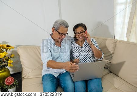 Older Couple Surfing The Web With A Laptop And A Mobile Phone. Two Smiling Old Men Sharing And Looki