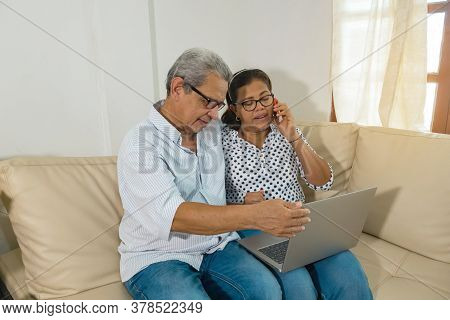 Older Latino Web-surfing Couple With Laptop And Cell Phone. Two Smiling Older Latinas Sharing And Lo
