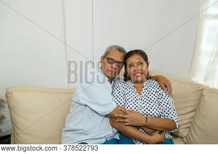 Happy Middle-aged Couple In Love Sitting On The Couch Hugging, Husband And Wife With Gray Hair Laugh