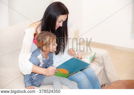 mother and daughter reading a book during a pandemic isolated