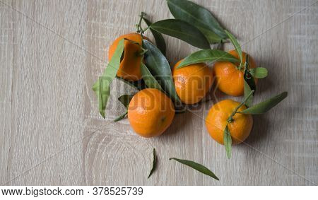 Tangerines Or Fresh Tangerines On A Wooden Background. Tangerines With Green Leaves. Organic Tangeri