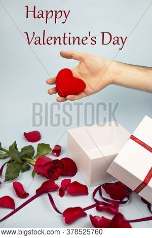 Valentine's Day Concept Valentine's Day. Male Hand Holds A Red Heart. White Gift On A Background Of