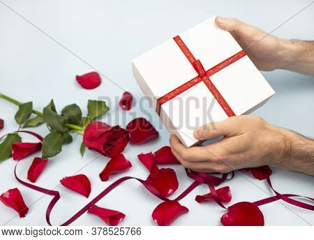 Valentine's Day Concept Valentine's Day. Male Hands Are Holding A White Gift Box On A Background Of